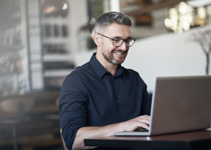 A bearded man sitting at a desk and working on his laptop