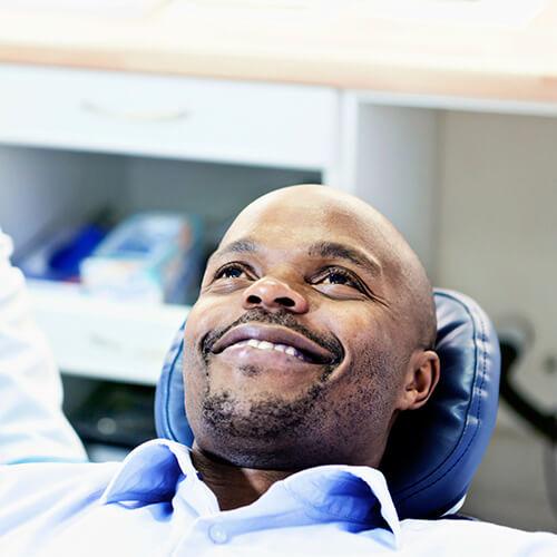 A bearded man reclining in a dental chair